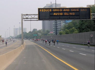 Image of sign on a highway asking commuters to reduce smog by not idling their vehicle.